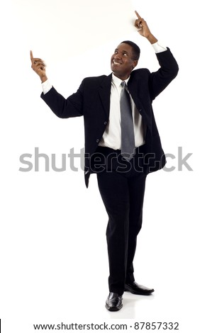 Full length a happy black businessman holding a blank sign above his head and looking at it  - isolated over white background