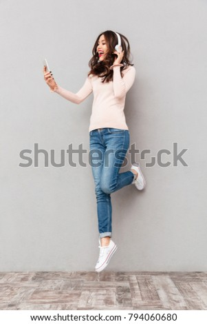 Full-length amazing female music lover wearing white headphones, taking pleasure in listening to music in smartphone over gray background