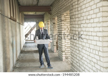 Full length architect looking comparing blue print paper plan housing project with building wearing yellow helmet Back view businessman in perspective long corridor with door perspective background - stock photo