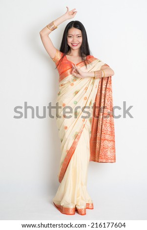 Full length Asian Indian female in dancing pose on plain background. - stock photo