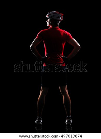 Full length back view of a cyclist in a black studio