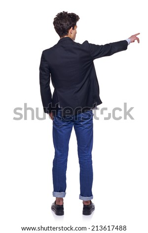Full length back view of young trendy man pointing to the side on blank copy space, over white background - stock photo