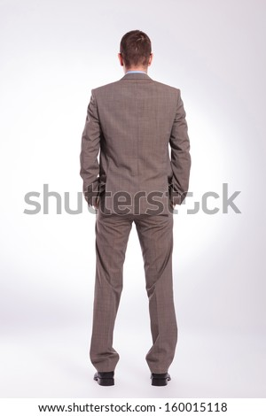 full length back view picture of a young business man standing with both hands in his pockets. on a gray background - stock photo