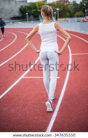 Full length. Back view. Young girl legs in stylish sneakers back side on red race track of stadium with white lane lines on background. Unrecognizable photo with copy space for inscription or objects
