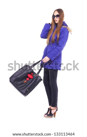 full length beautiful fashionable woman in blue coat with handbag posing