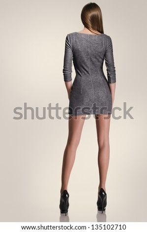 full length beautiful girl in the dress from back on the studio background - stock photo
