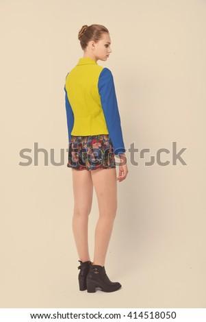 Full length beautiful young woman standing in studio - stock photo