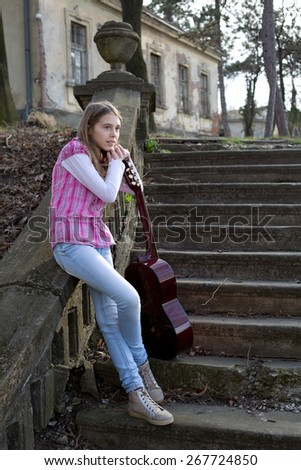 Full Length Body Shot of Teenage Pensive Girl with Crossed Legs Leaning on the Guitar, Side View - stock photo