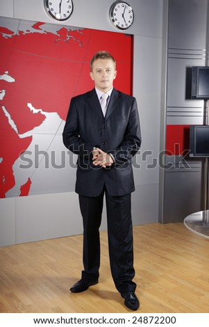 full length business man standing up in front of the camera in television news studio - stock photo