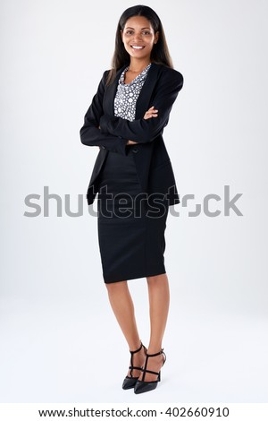 Full length business woman portrait wearing a black suit, smiling with arms crossed - stock photo