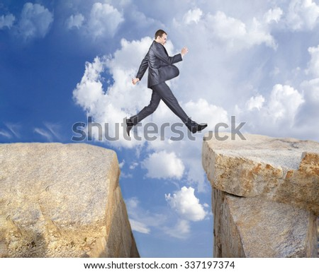 Full length businessman or Manager jumping from a rock to another. Business Man fly over the mountains