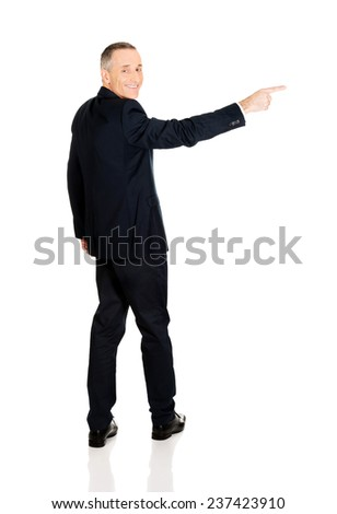 Full length businessman pointing right. - stock photo