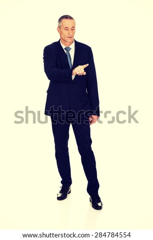 Full length businessman pressing abstract button.
