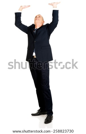 Full length businessman pushing invisible ceiling. - stock photo