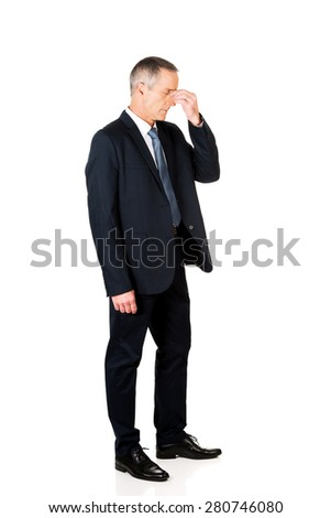 Full length businessman suffering from sinus pain. - stock photo