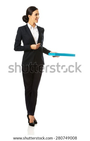 Full length businesswoman giving a binder. - stock photo