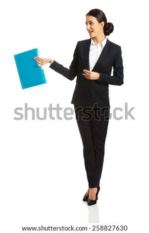 Full length businesswoman holding a binder. - stock photo