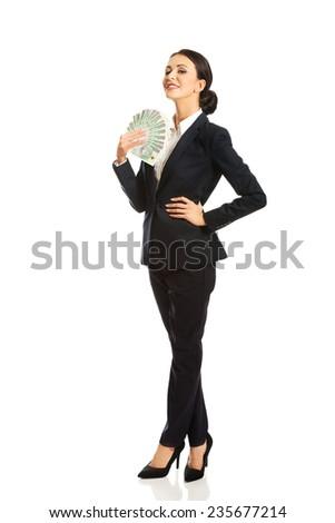 Full length businesswoman holding a clip of polish money. - stock photo