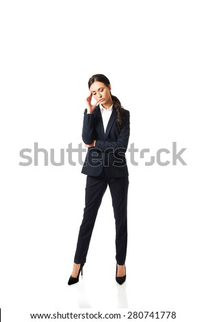 Full length businesswoman tired because of troubles holding her head. - stock photo
