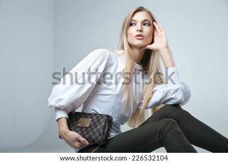 Full length casual young fashionable woman sitting with a bag in light background - stock photo