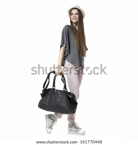 Full length casual young woman in cap with a black bag walking in studio - stock photo