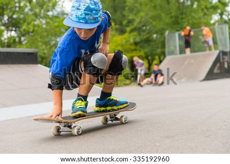 Full Length Close Up of Young Boy Crouching on Skateboard in Skate Park with Other Skaters in Background on Ramp - stock photo