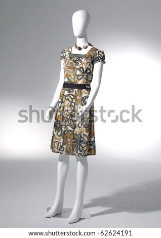 full-length collection of dress on mannequin in light background - stock photo