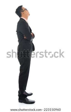 Full length confident southeast Asian business man crossed arms looking away standing isolated on white background. - stock photo