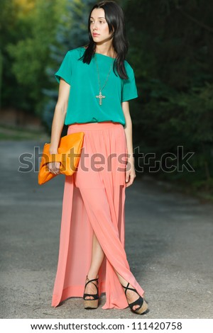 Full length fashion girl in menthol blouse and long chiffon skirt posing outdoors