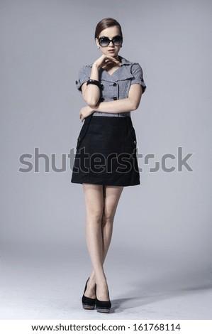 full length fashion girl in sunglasses posing gray background - stock photo