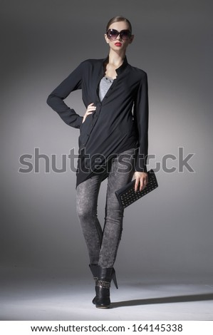 Full length fashion girl wearing modern sunglasses holding purse walking in studio - stock photo