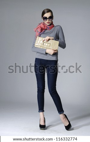 full-length fashion girl with handbag posing over gray background - stock photo