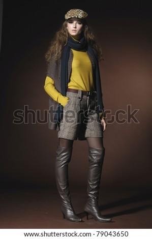 Full length fashion model in a cap posing - stock photo