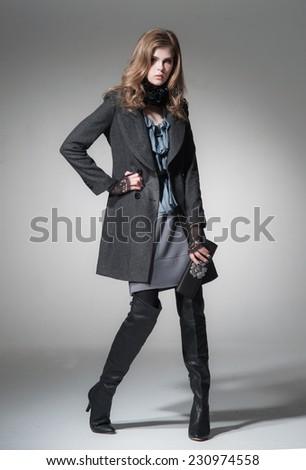 full-length fashion model in coat holding little purse posing on light background  - stock photo