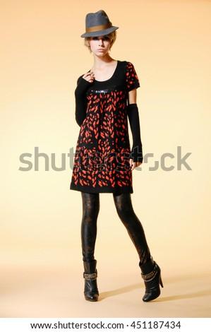 full-length fashion model in hat holding handbag posing - stock photo