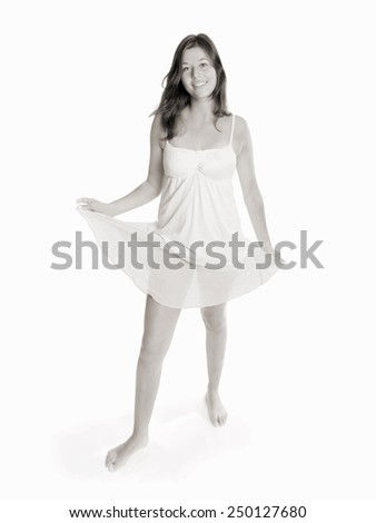 Full length fashion portrait of a beautiful young woman dancing barefoot, monochrome photo, isolated in front of white studio background - stock photo