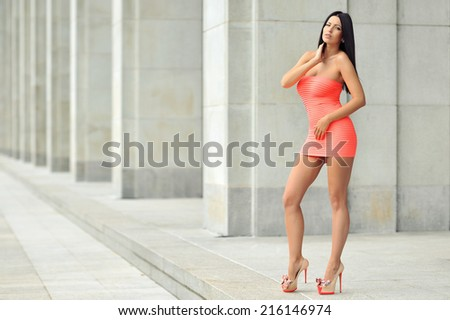 Full length fashion portrait of beautiful woman in red dress posing in the city - stock photo
