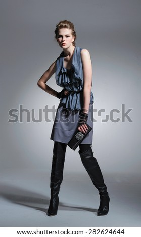 full-length fashion two model in coat clothes with purse posing on light background  - stock photo