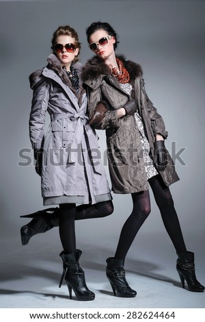 full-length fashion two model in coat clothes with sunglasses posing on light background  - stock photo