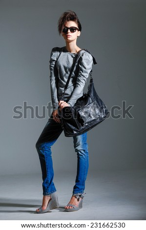 Full length fashion woman studio in jeans with bag on gray background - stock photo