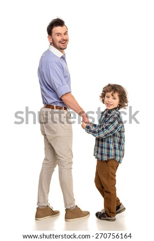 Full length. Father and son standing with back to the camera and holding hands,isolated a white background. Looking at camera. - stock photo