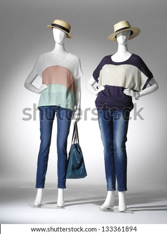 full-length female clothes on a two mannequin with bag in light background - stock photo