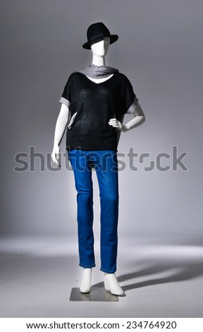 full-length female in jeans with hat on mannequin on gray background - stock photo