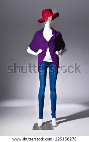 full-length female in jeans with red hat on mannequin on gray background - stock photo