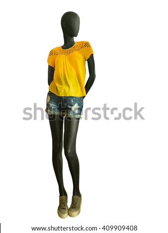Full-length female mannequin clothing in yellow blouse with embroidery jeans shorts, isolated on white background. No brand names or copyright objects. - stock photo