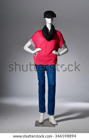 full-length female with red dress in cap on mannequin in light background - stock photo