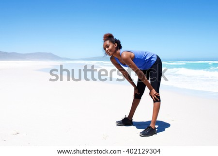 Full length fit young woman standing with her hands on knees. Female taking a break during workout on the beach. - stock photo