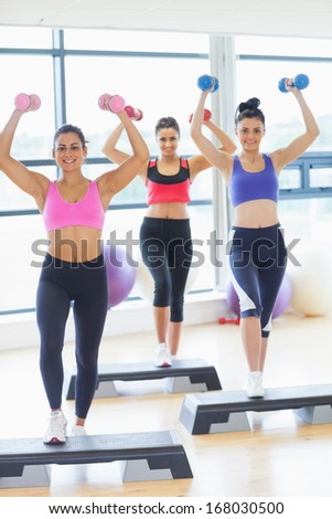 Full length fitness class performing step aerobics exercise with dumbbells in a gym - stock photo