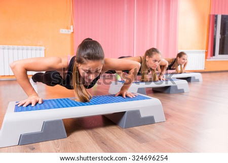 Full Length Front View of Group of Young Women Doing Push Ups or Plank Exercises in Step Class Using Step Platforms and Looking Down in Concentration - stock photo