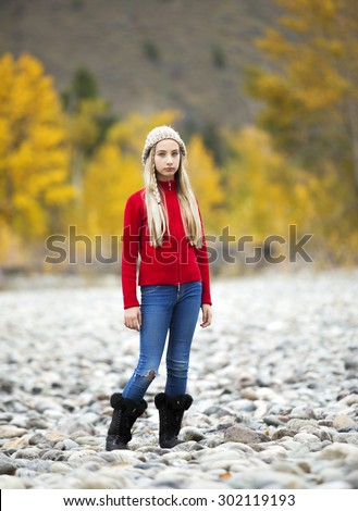 Full length, front view photo of pretty, young girl standing in a nature setting with autumn colors in background